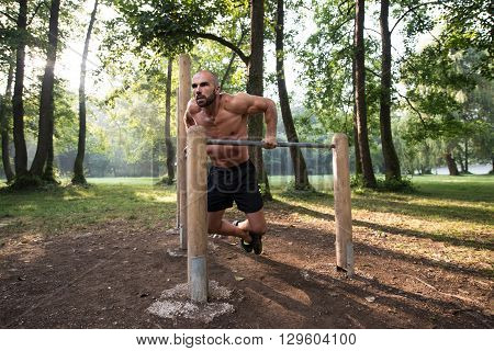 Man Exercising On Parallel Bars Outdoors