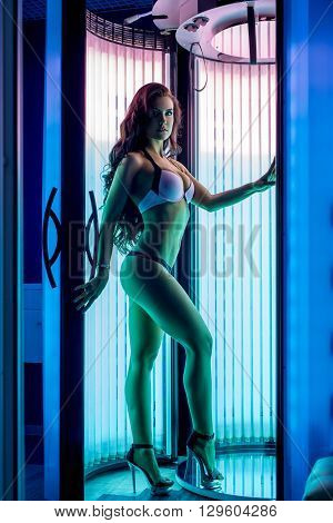 Pretty woman posing while tans in modern tanning booth