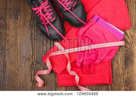 Pair of sneakers jumper t-shirt and sports bra on the wooden background