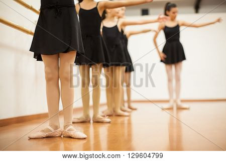 Closeup of a group of girls and their dance teacher learning ballet in a dance academy