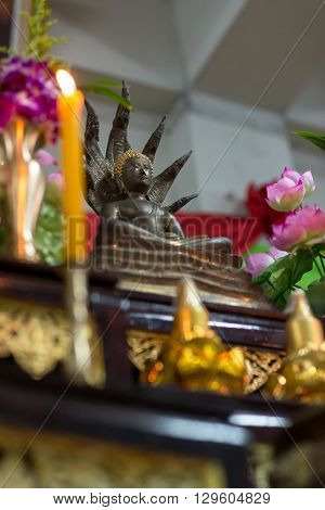 A statue of Lord Buddha with Nagas on a pedestal with offerings.