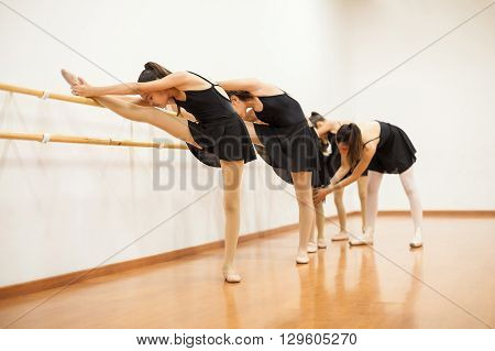 Group Of Girls Touching Knees On A Barre