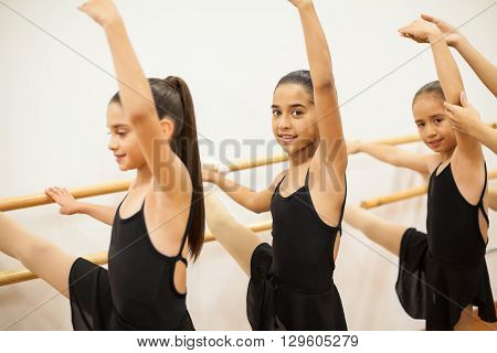 Pretty girls standing next to a barre with their leg up during a ballet class at school