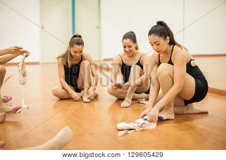 Several women sitting on the dance floor getting ready and putting their shoes on before dance practice