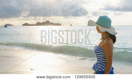 Young girl wearing a hat and swimsuit standing watch nature sky and sea during the sunrise on beach of Honeymoon Bay at Koh Miang Similan Islands National Park Phang Nga Thailand 19:6 wide screen