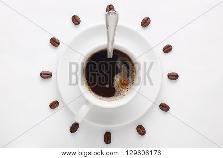 Coffee cup with spoon on saucer and coffee beans against white background forming clock dial viewed from above as symbol of morning, energy and cheerfulness