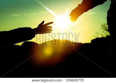 Helping hands with sunlight between two climbers
