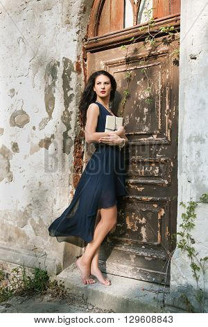 mistery barefoot beautiful girl in blue romantic dress with book near the vintage wooden door. fairy tale legend