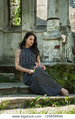 beautiful girl in a long dress sitting on old steps with a branch of lilac