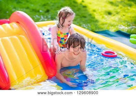 Children playing in inflatable baby pool. Kids swim and splash in colorful garden play center. Happy boy and girl playing with water toys on hot summer day. Family having fun outdoors in the backyard.