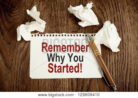 Remember Why You Started. Written on white paper on wooden background
