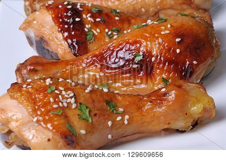 Fried chicken leg with sesame seeds in a plate closeup