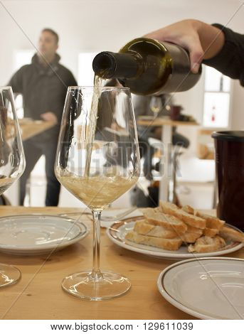 White wine poured into a glass from a bottle at a wine tasting with some blurred people in the background