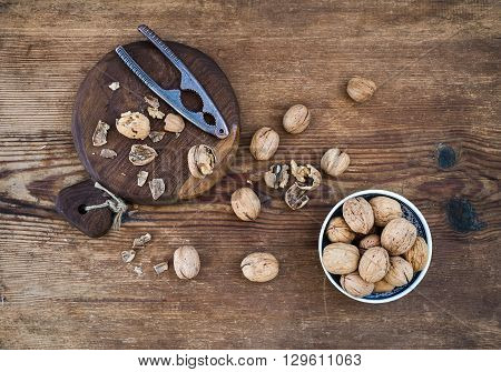 Walnuts in ceramic bowl and on wooden board with nutcracker over rustic wooden background, top view
