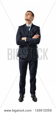 Cutout businessman stands with folded arms looking up. Thinking process. The emergence of new ideas. Success and development. Business staff. Office clothes. Dress code. Presentable appearance. Successful lifestyle.