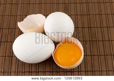 Fresh eggs with one broken open egg