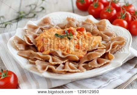 Wholegrain Pasta with stracchino cheese and fresh tomatoes close up