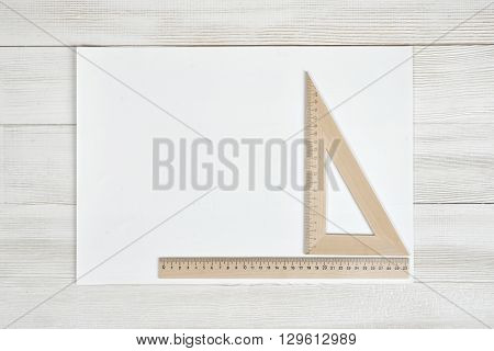White paper with triangle centimeter ruler and simple centimeter ruler. Top view composition. Measuring process. Work place of draftsman, architect, constructor. Engineering work. Construction and architecture. Architect drawing. Measurement. New project.