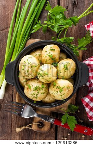 boiled new potato with fresh greens on table