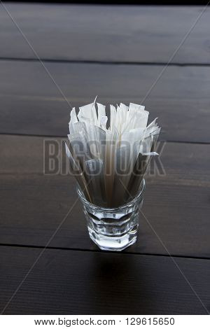 packed toothpicks in glass on wooden table