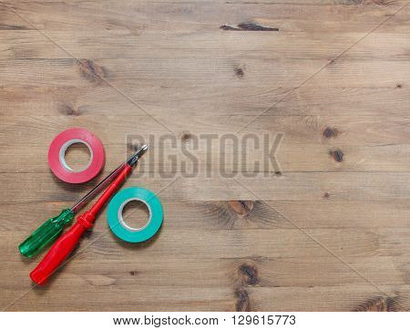 multicolored screwdrivers insulating tapes on wooden table