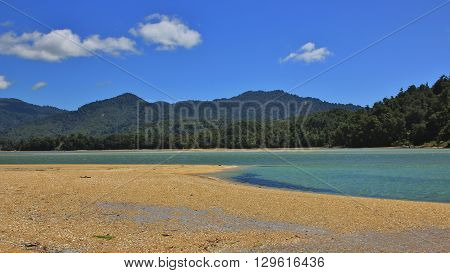 Landscape in the Abel Tasman national park. Awaroa Inlet. Sandy beach blue water and green hills.