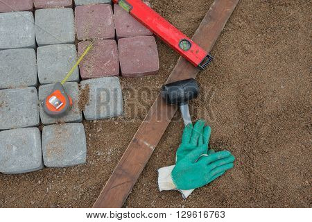 Pavement details, stone blocks rubber hammer level gloves and tape measure