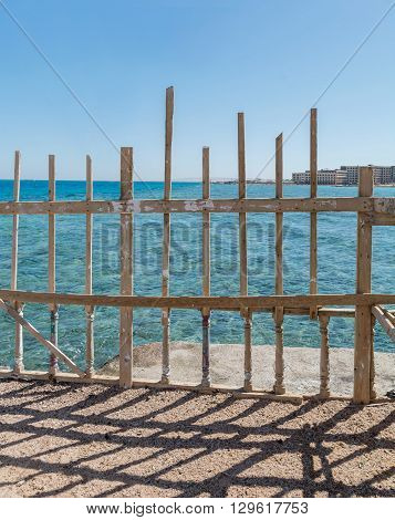 Seaside brown and green wooden fences against aqua ocean and blue sky