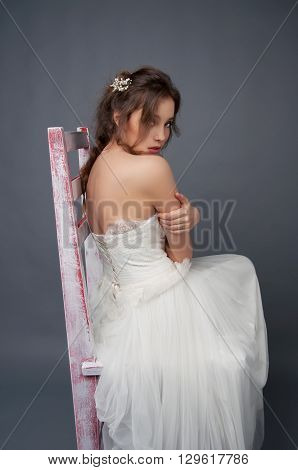 Young bride sitting alone on a stool in wedding dress wearing beaded headpiece