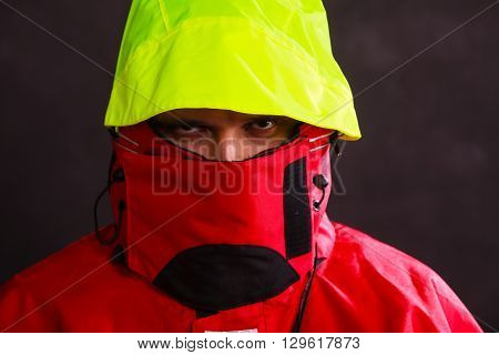 Male outdoorsman with covered face. Young man wearing waterproof oilskin. Adventure outdoor action danger concept.