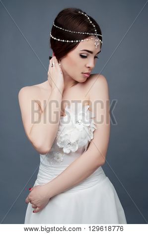 Brunette bride wearing tikka headpiece and white wedding dress. Bridal makeup and fashion.
