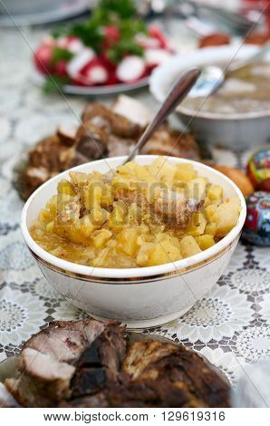 Vertical selective focus shot of an assortment of meals. Mashed Potato with pork ribs in bowl with serving spoons. Meal accompanied with slices of boiled salted pork sausage boiled eggs radish fresh vegetables
