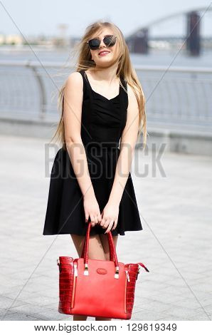 Full length outdoor portrait of a beautiful young blonde in black dress blouse sunglasses and handbag on a light background