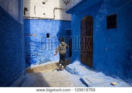 Chefchaouen Morocco - April 10 2016: A child running in a street of the town of Chefchaouen in Morocco.
