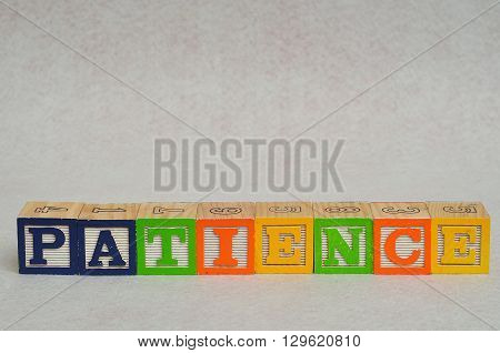 The word patience spelled with colorful alphabet blocks isolated on white background