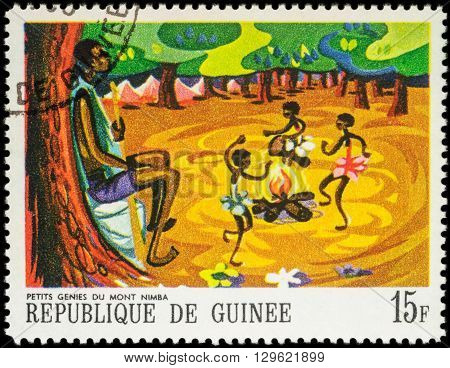 MOSCOW RUSSIA - MAY 12 2016: A stamp printed in Guinea shows three little black girls dancing around the fire series