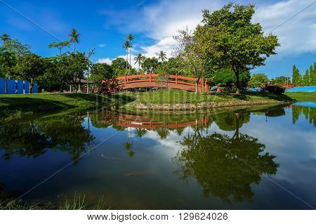 Landscape of tropical lake with bridge and reflection of water over sunny day at Damai garden,Labuan,Malaysia.
