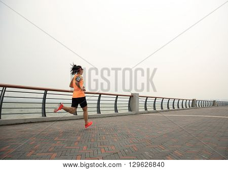 young asian woman runner running on seaside