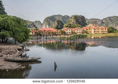 View of a shallow lake in Hoa Lu located at Ninh Binh in Vietnam. On the background, empty boat, limestone karst with lush green hillscape and resort buildings are seen.