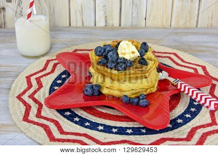 Waffle stack with blueberries, butter and syrup on red star plate with white milk in retro glass bottle.
