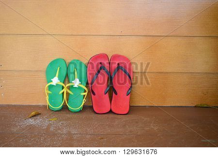 Red and Green flipflop sandals on wooden wall