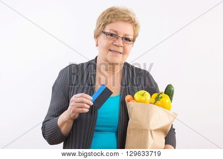 Elderly senior woman with fruits and vegetables in shopping bag holding credit card paying for shopping and healthy nutrition in old age