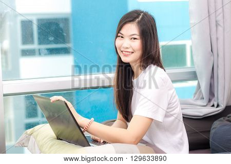 Asian Woman Lying On The Bed Using A Laptop