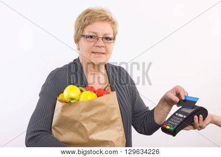 Elderly senior woman holding shopping bag and using payment terminal with contactless credit card cashless paying for shopping healthy nutrition in old age