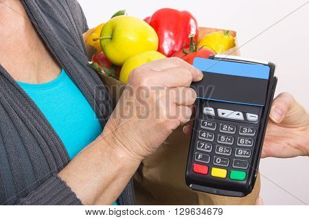 Hand of senior woman using payment terminal with contactless credit card cashless paying for shopping healthy nutrition