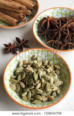 An assortment of whole dried spices presented in colorful small ceramic bowls - cinnamon sticks star anise and cardamom pods.