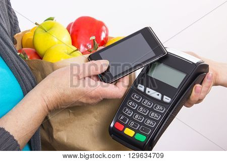 Hand of woman using payment terminal with mobile phone with NFC technology cashless paying for shopping