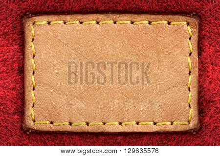 Blank yellow leather label on red carpet background