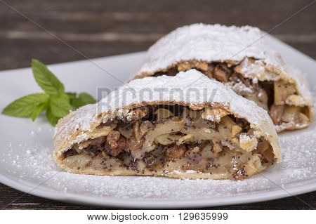 Slice of an apple strudel on a white plate close up