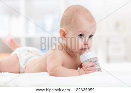 Infant baby drinking water from bottle lying on bed. Child weared diaper in living room.